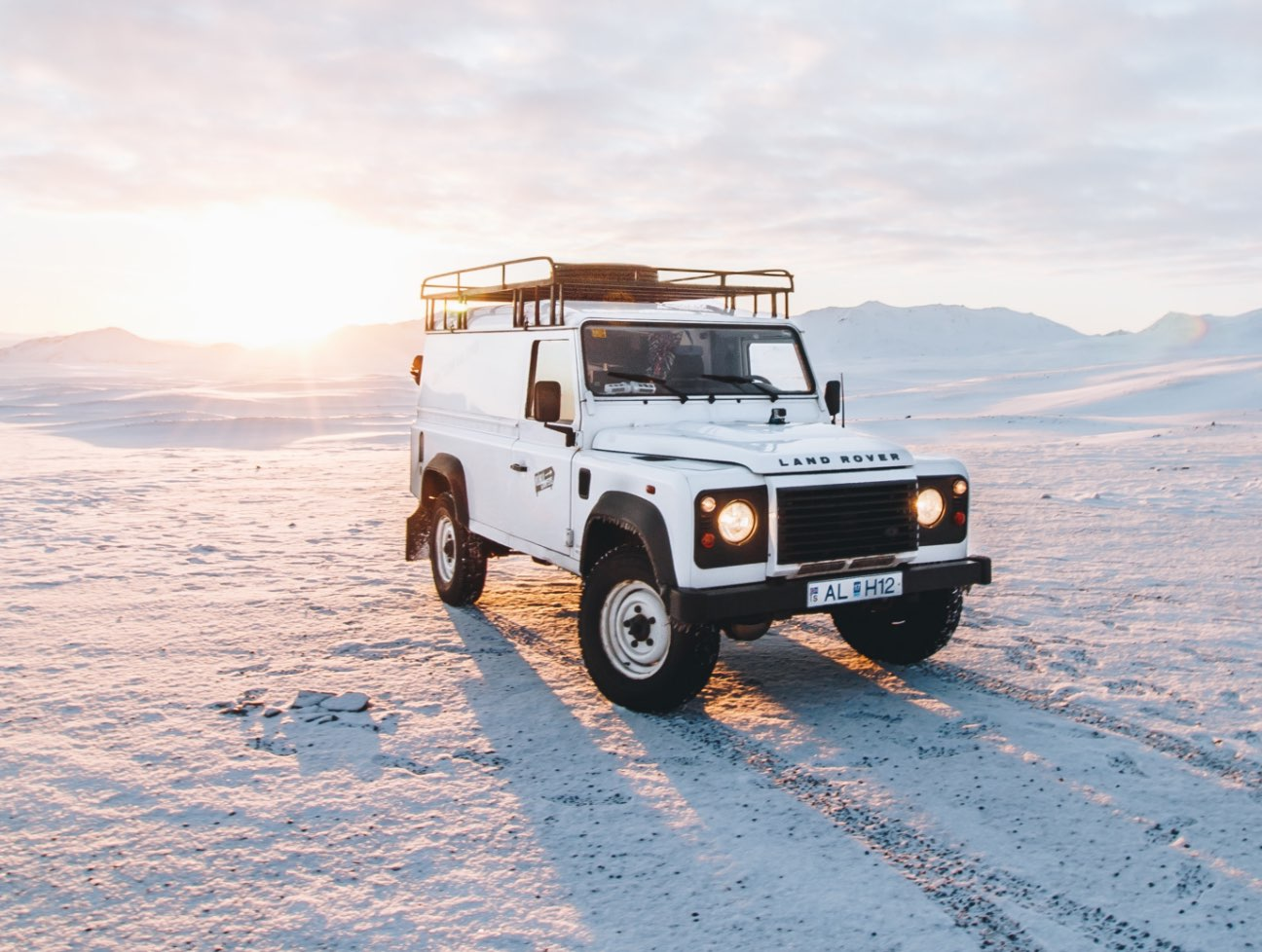 Land Rover parked on dunes at sunset