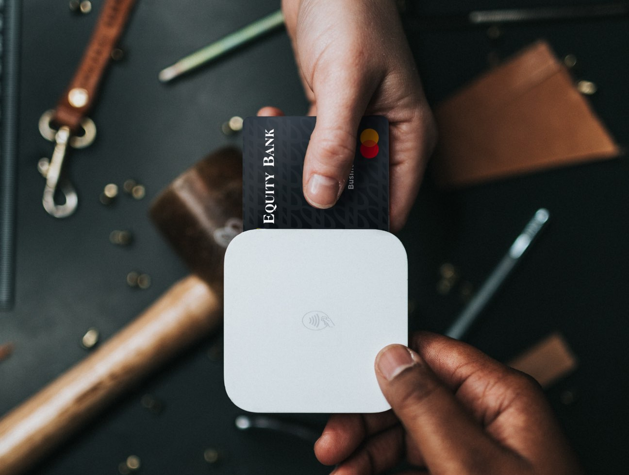 Equity credit card with hand inserting into payment Square