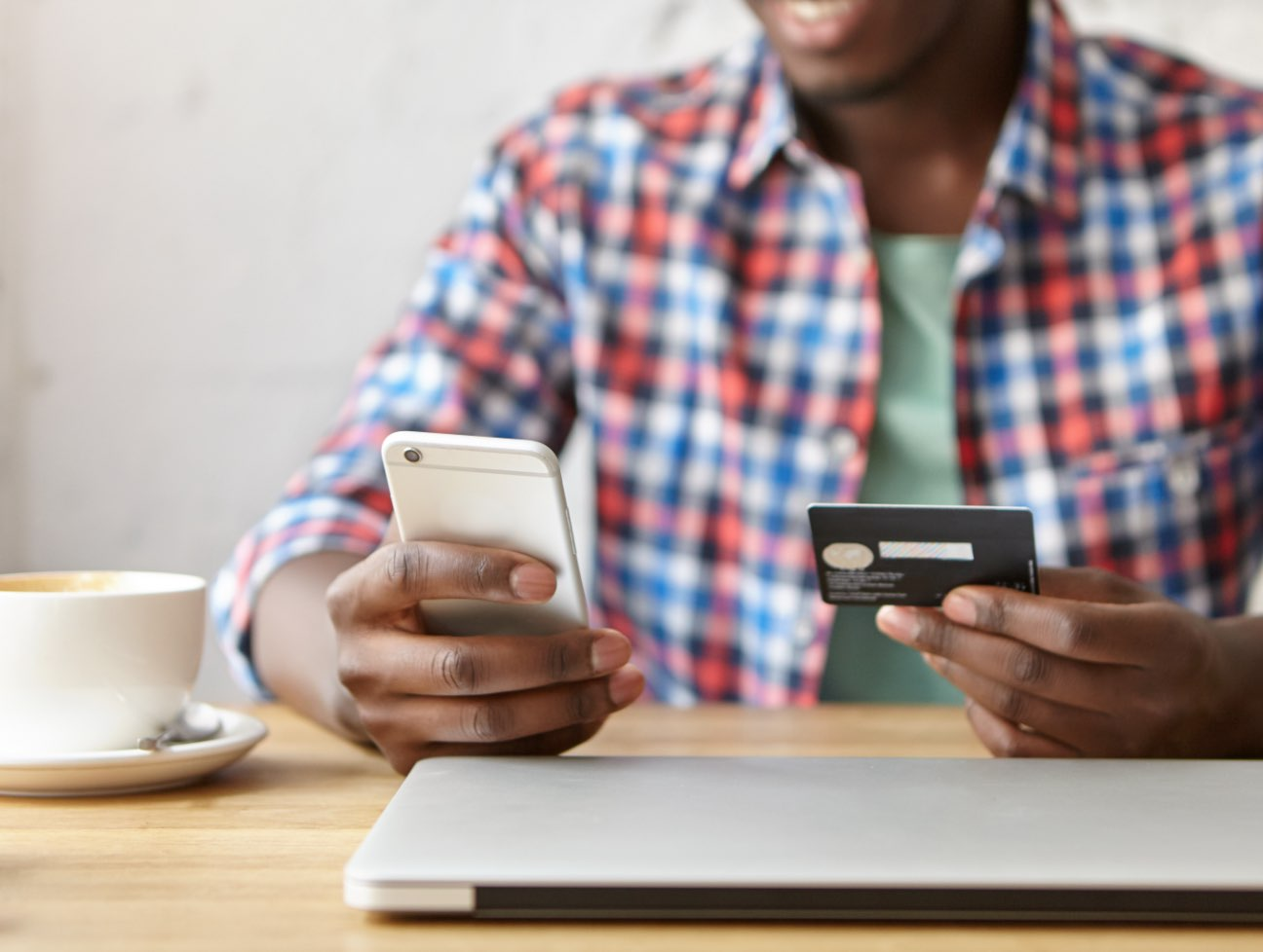 Person holding a cell phone and a payment card