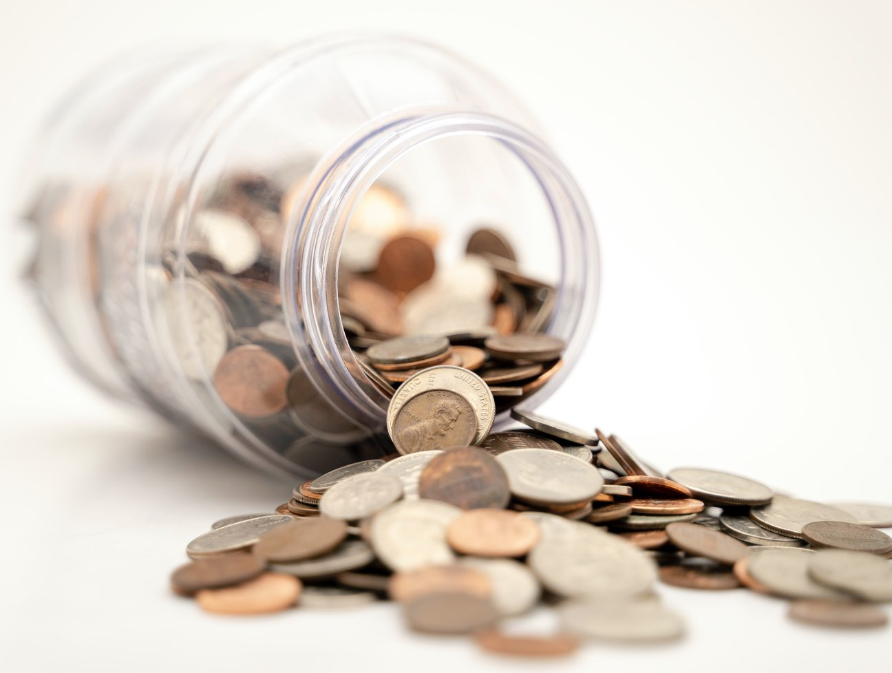 A jar of change on its side with coins spilling out.