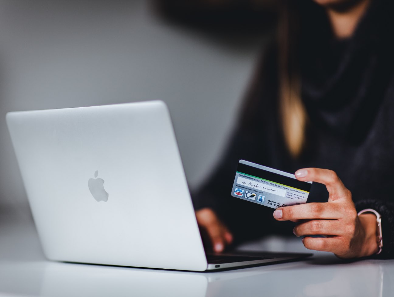 Hand holding credit card in front of laptop