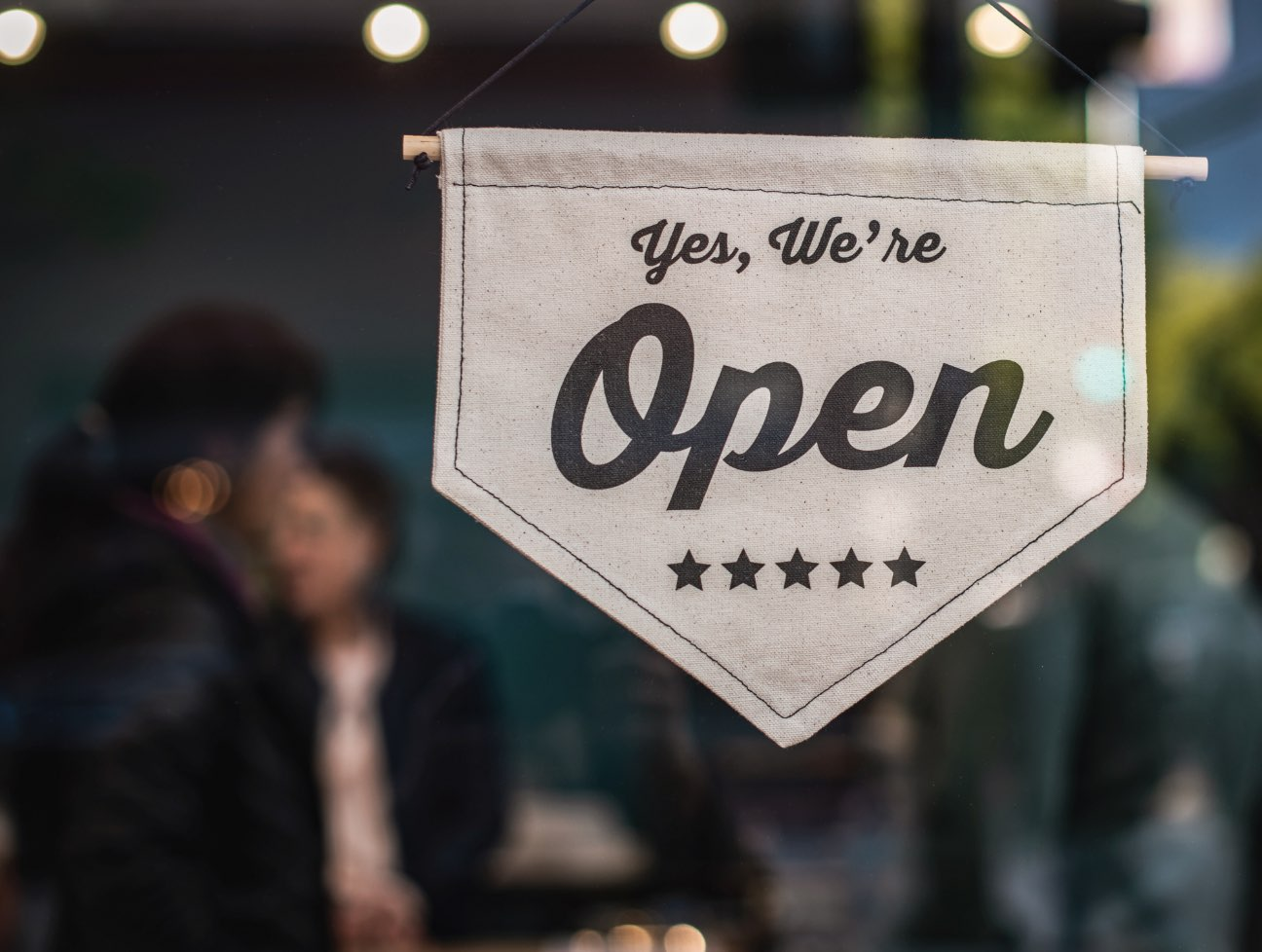 A 'We're Open' flag sign hanging in store window