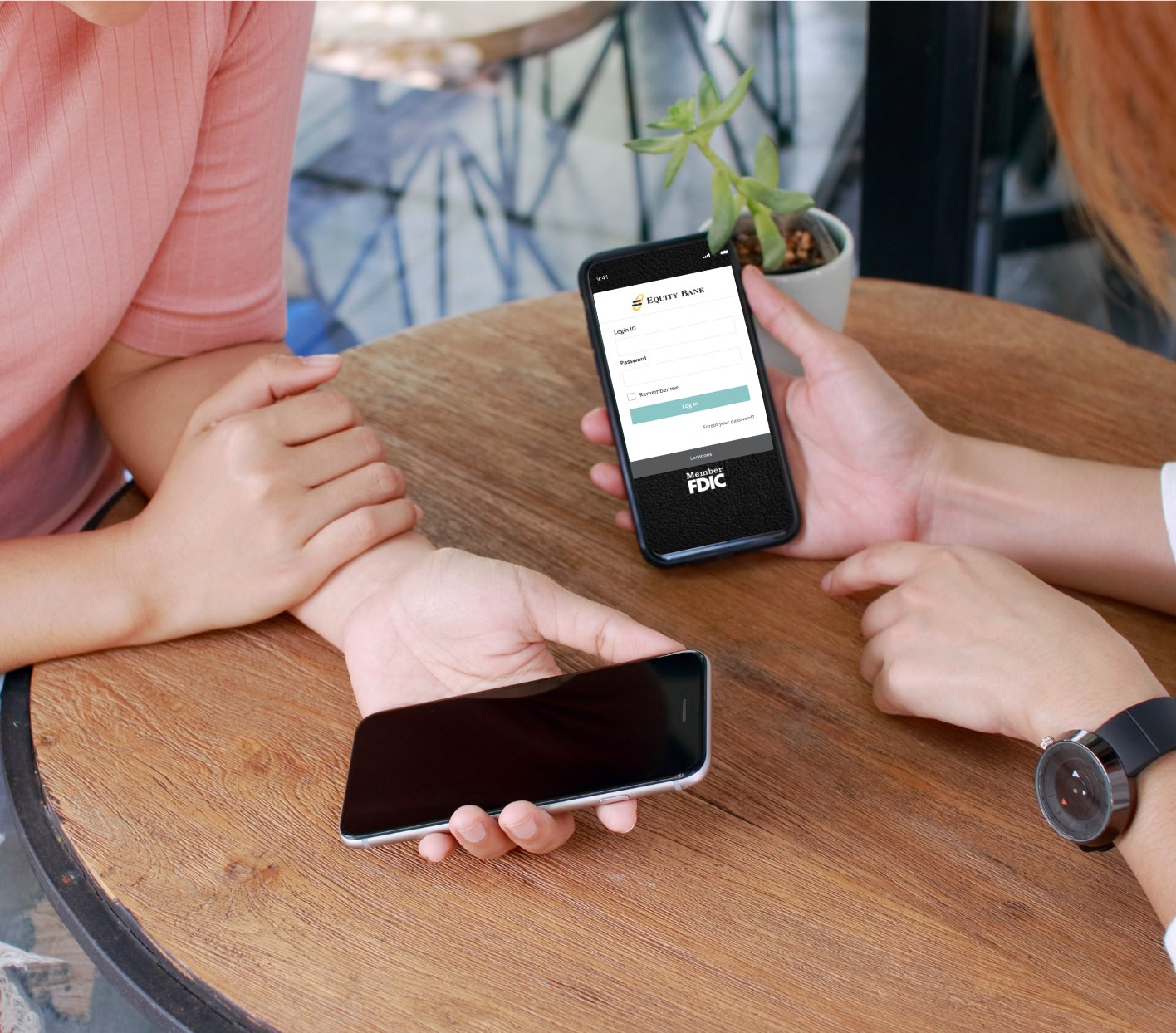 Two people holding phones over a table using the banking app