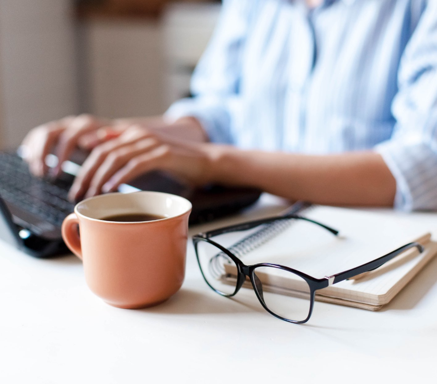 close-up view of person sitting at desk with computer, coffee and glasses