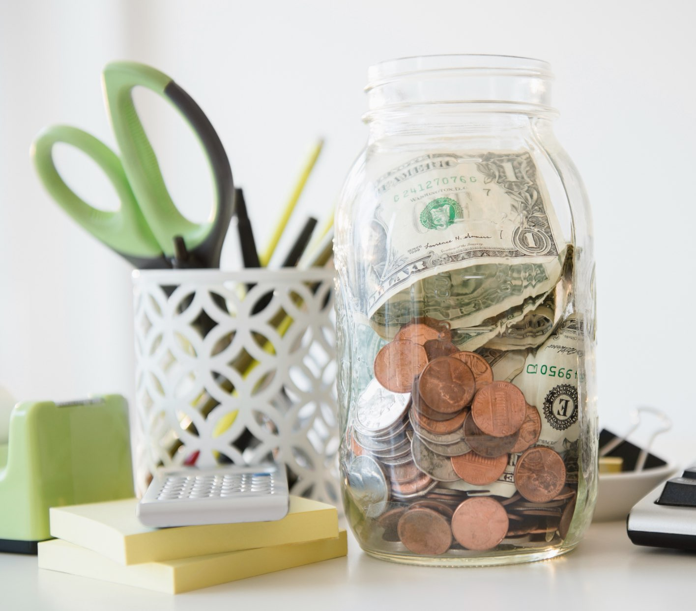 A jar of money and change on a desk.