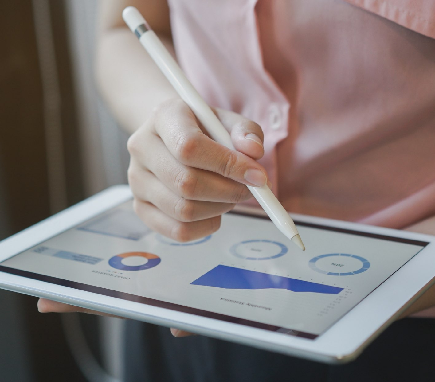 A woman's hand holding a stylus pointing to an ipad with charts and graphs
