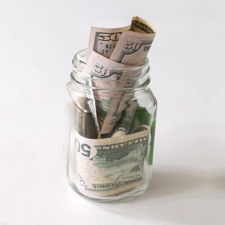 A clear glass jar full of money bills