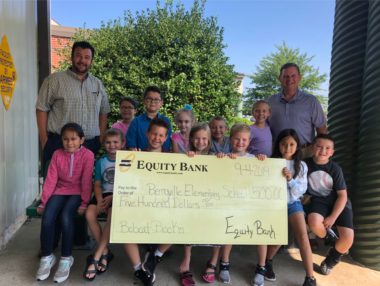 Group of school kids with teachers holding a large Equity Bank donation check.